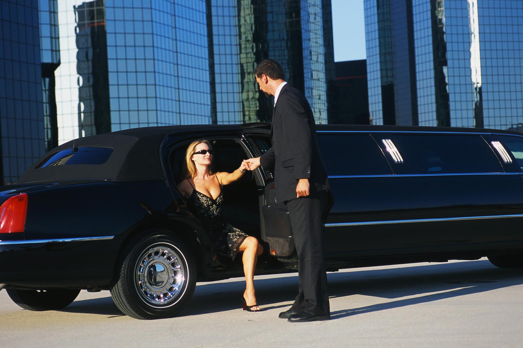 Viajes exclusivos con LimussineCC - mujer bajando de limusine ayudada por el conductor